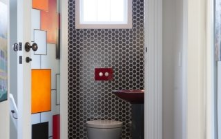 Nicola Manning Design award winning powder room with red and orange stained glass door and vessel basin and pendant light