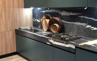 Eurocucina kitchen seen in Milan with black marble bench top and splash back with dark teal cabinetry with light timber
